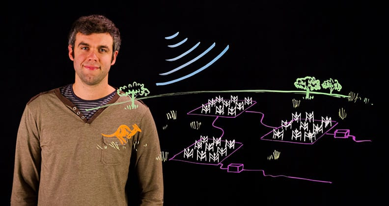 MOOC teacher John Morgan standing in front of a drawing of astronomy equipment