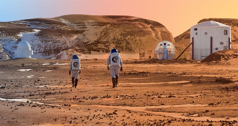 Two people in spacesuits walking across a Mars-like desert towards a research station.