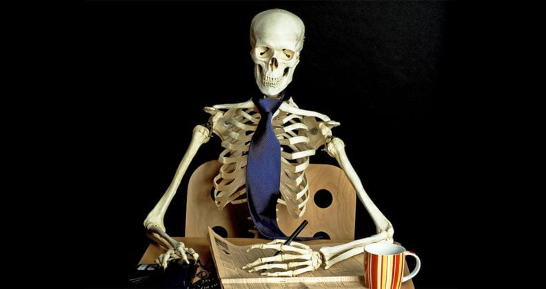 A skeleton sits at an office desk