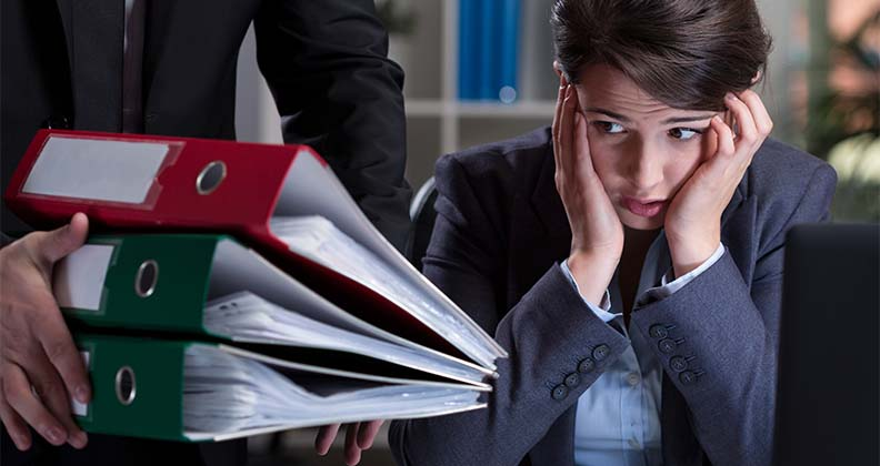 Girl looking overwhelmed siting at desk with lots of files.