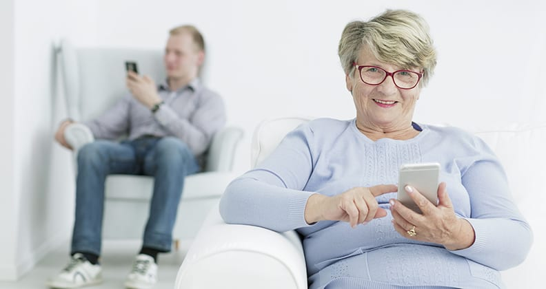 Elderly woman sitting down holding a phone with man sitting behind her.