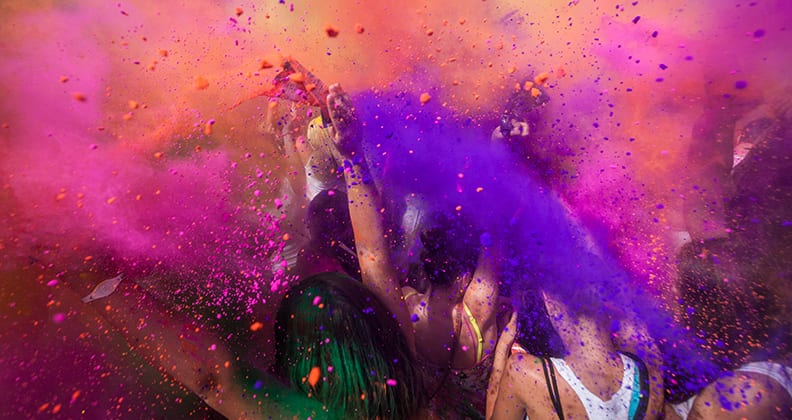 A group of students throwing colour bombs to celebrate Holi Festival