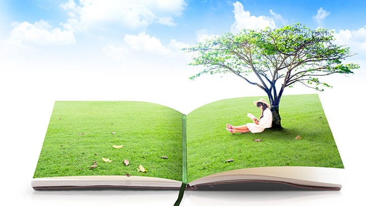 girl sitting and reading under tree on book with grass pages