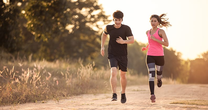 Young Asian couple running along a track