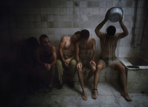 Five men rest quietly in a dimly lit white-tiled old bathroom