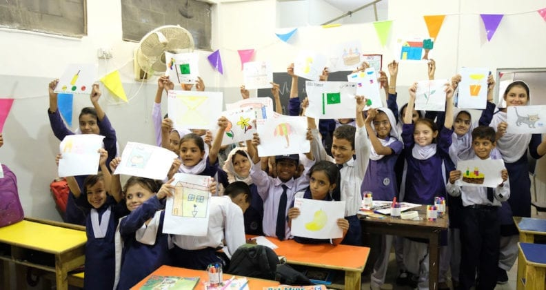 Girls from Anum School in Karachi, Pakistan, proudly display their artwork in a classroom.