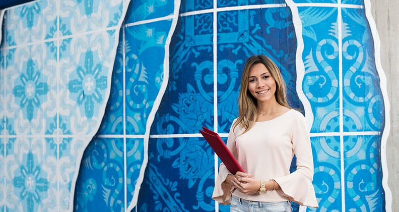 Student standing in front of colourful blue background
