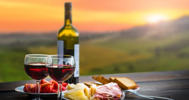 Wine bottle, glasses of wine, and cheese and cold meat platter on bench top overlooking a vineyard.
