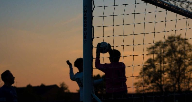Silhouette of goalkeeper catching ball at sunset