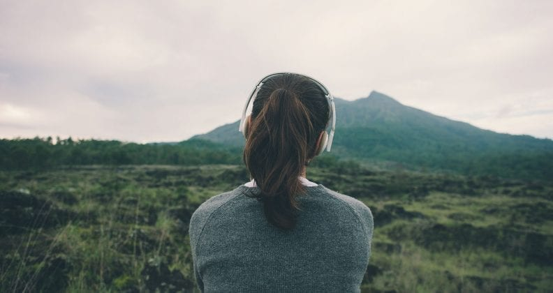 Woman looking at mountain wearing headphones