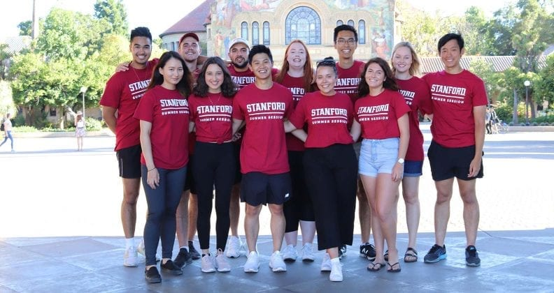 Group of students posing in Stanford tee-shirts on campus