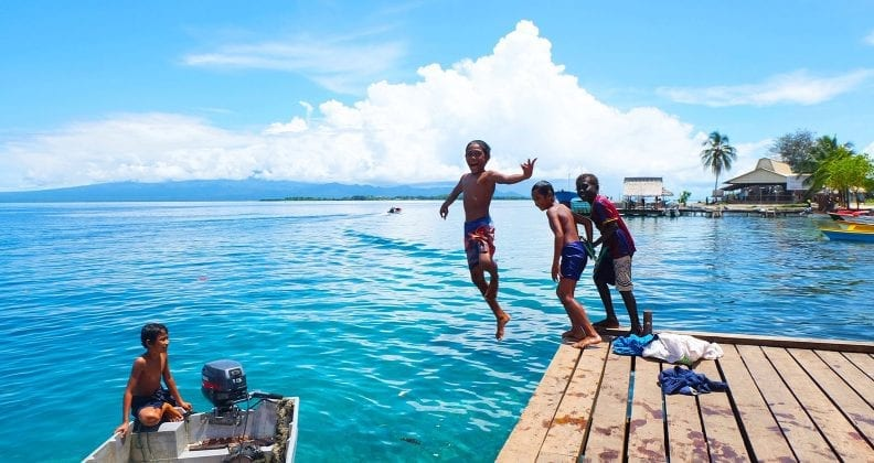 A young boy jumps off a jetty into aqua waters, while his three friends look on.