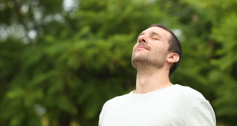 Relaxed adult man breathing fresh air in a forest with green trees in the background .