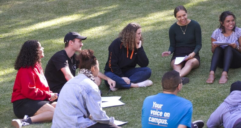 A group of Curtin University students participating in a yarning circle.