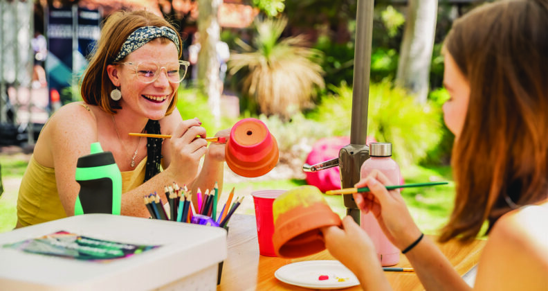 Two females smile at each other while they paint plant pots with bright coloured paint