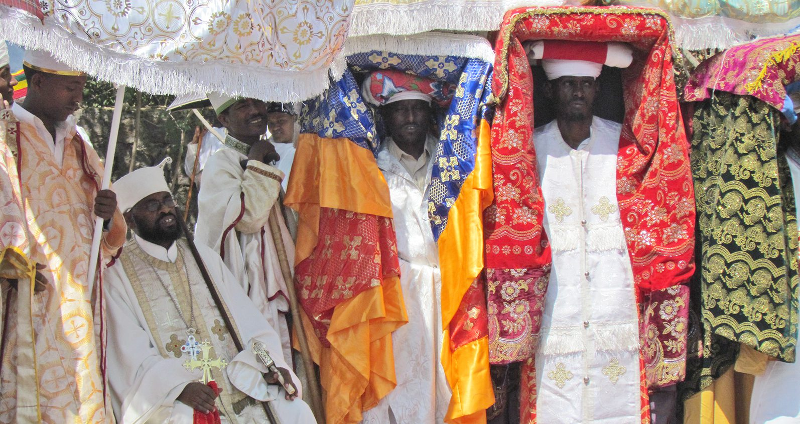Priests from the Ethiopian Orthodox Church carrying wrapped tabots above their heads.